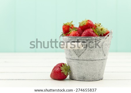 Strawberries on a bucket over a white wooden table with a turquoise background - stock photo