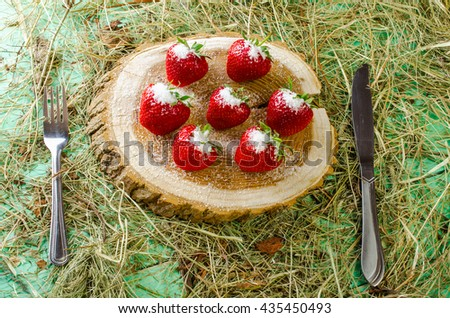 Strawberries on the stump, sprinkled with sugar. Hay and fork with the knife beside him. - stock photo