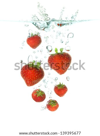 strawberries splash in clear water isolated on white - stock photo