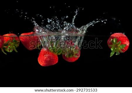 Strawberries splashing into water on a black background - stock photo