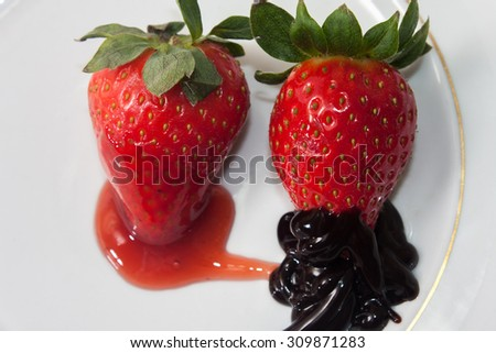 Strawberries topped with chocolate and strawberry syrup. - stock photo