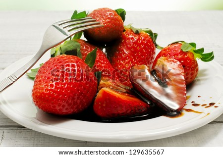 strawberries with balsamic vinegar over ceramic plate - stock photo