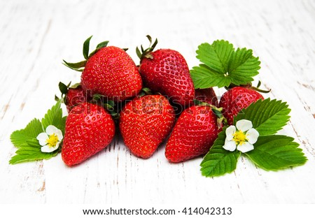 Strawberries  with leaves on a old wooden background - stock photo