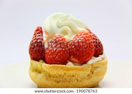 Strawberries with whip cream on top in a bread bowl. - stock photo