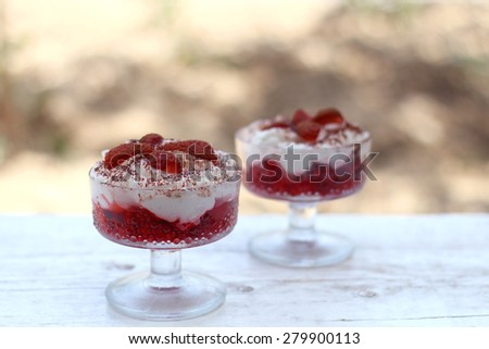 Strawberries with whipped cream and cocoa powder in decorative glass bowls. White rustic table, summer background, selective focus.  - stock photo