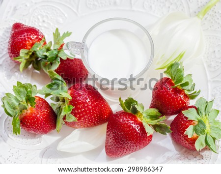 strawberry and glass of milk on white background - stock photo