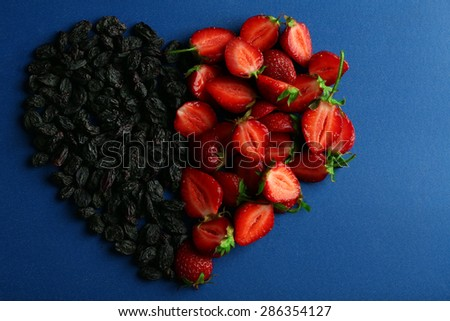 Strawberry and prunes in shape of heart on blue background - stock photo