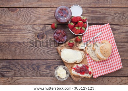 Strawberry berries, Strawberry jam, butter and bread on wooden table. Breakfast with fruits top view horizontally. Macro shot selective focus - stock photo