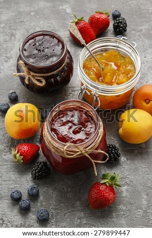 Strawberry, blueberry and peach jams in glass jars - stock photo