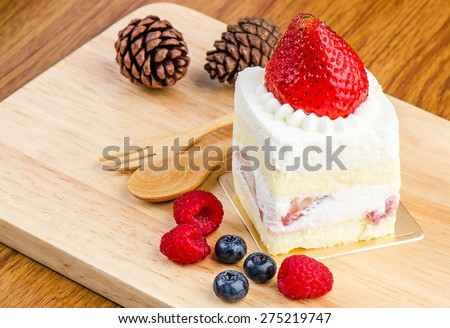 Strawberry cake on wooden background, Cake with strawberries, Piece of cake, raspberries and blueberrys. - stock photo