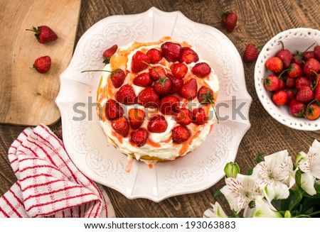 Strawberry cake with whipped cream in wooden table - stock photo