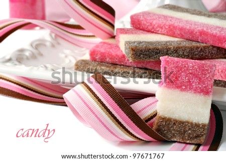 Strawberry, chocolate, and vanilla coconut candy on ceramic plate with color coordinated ribbon.  Macro with shallow dof.  (Text is on solid white and easy to remove.) - stock photo