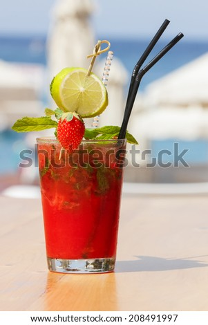 Strawberry cocktail on blurred beach background. Outdoor settings - stock photo