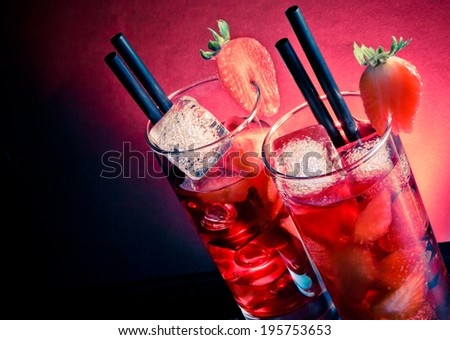 Strawberry cocktail with ice on wood table and space for text on blue and pink light disco club atmosphere - stock photo