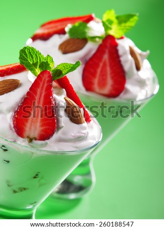 Strawberry cream in a glass garnished with strawberries, almonds and fresh mint - stock photo