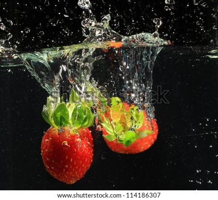 strawberry drop in water - stock photo