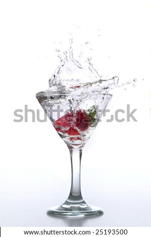 Strawberry dropped into a martini glass isolated on white - stock photo
