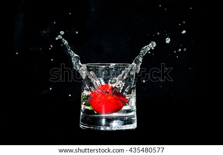 Strawberry falling into a glass of sparkling water and creating a splash - stock photo
