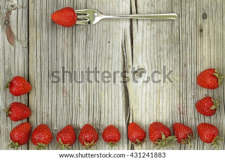 Strawberry frame and Ripe strawberry on a fork on a worn wooden background. free space for your text. - stock photo