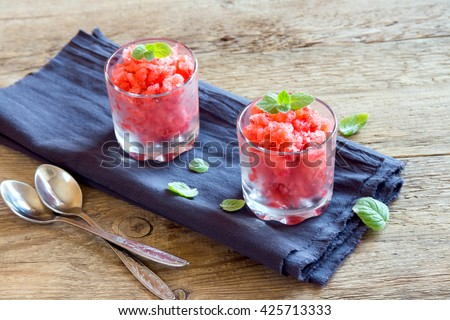 Strawberry granita with mint (frozen dessert) in portion glasses on rustic wooden background with copy space - stock photo