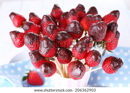 Strawberry in chocolate on skewers in cup on table close-up - stock photo