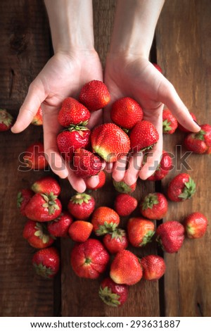 strawberry in hand on the background of the table which also strawberries - stock photo