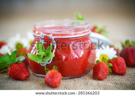 strawberry jam in a glass jar with strawberries on a table - stock photo