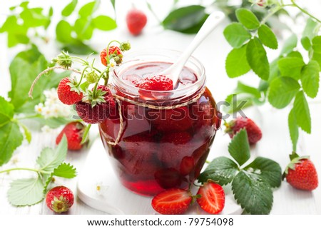strawberry jam in a jar and fresh berries on the wooden table - stock photo