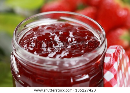 Strawberry jam in a jar, decorated with fresh strawberries - stock photo