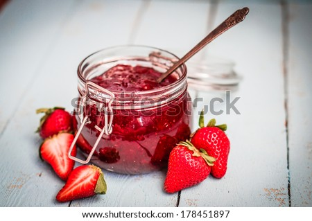 Strawberry jam in a jar on wooden background - stock photo