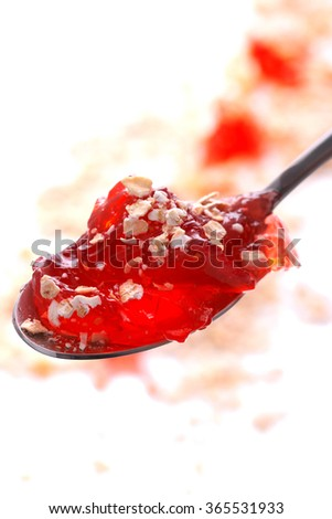 Strawberry jelly with oatmeal in the spoon. Isolated photo. - stock photo