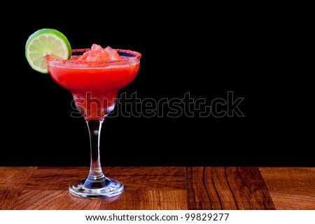 strawberry margarita isolated on a black background served on a bar top - stock photo