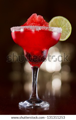 strawberry margarita on a bar top with a busy out of focus background - stock photo