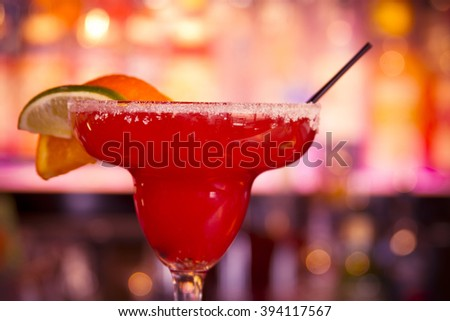 Strawberry margarita on the rocks with salt on glass rim and garnished with orange, lemon and lime slices sitting on bar in front of bar lights - stock photo