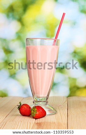 Strawberry milk shake on wooden table on bright background - stock photo
