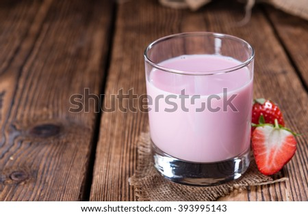 Strawberry Milk with fresh fruits on an old wooden table - stock photo