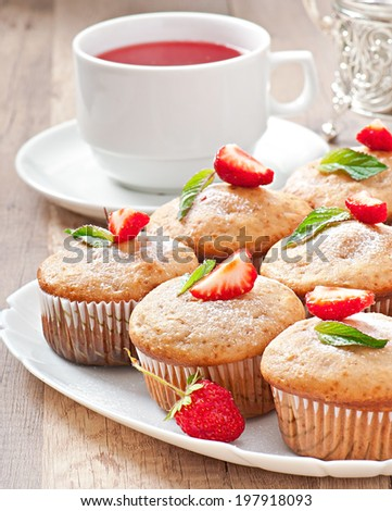 Strawberry muffin on a white plate with a fresh strawberry - stock photo