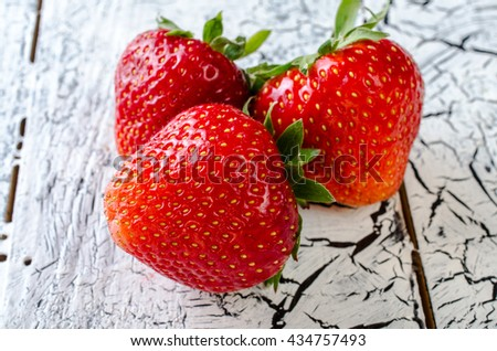 Strawberry on a bright wooden background. Close-up. - stock photo