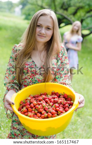 Strawberry pickers: front girl happy smiling & looking at camera on summer green outdoors background - stock photo