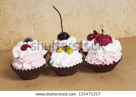 Strawberry pink cupcakes with fruit on top on a brown background - stock photo