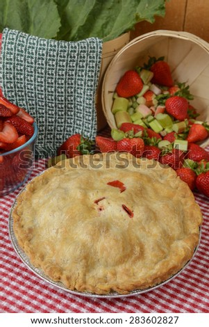 Strawberry-Rhubarb Pie on a country table with strawberries and rhubard and a red and white checkered table cloth - stock photo