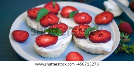 Strawberry sandwich with soft cheese, ripe berries and leaves of mint. Food composition on a blue background. Selective focus. - stock photo
