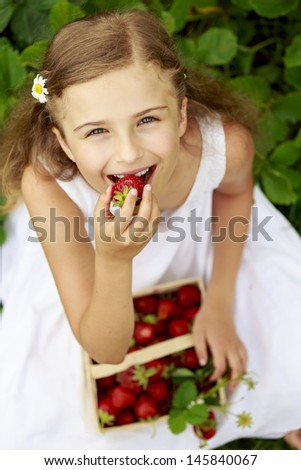 Strawberry season - young girl eating fresh picked srawberries in the garden - stock photo