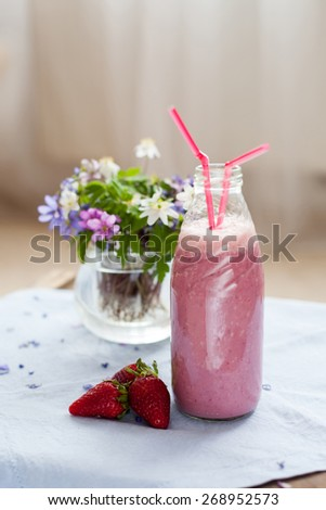 Strawberry smoothie freshly made in a jar with a lined straw, forest spring flowers in a vase behind the bottle - stock photo