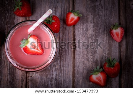 Strawberry smoothie in glass jar, over old wood table. Vintage effect with intentional vignette - stock photo