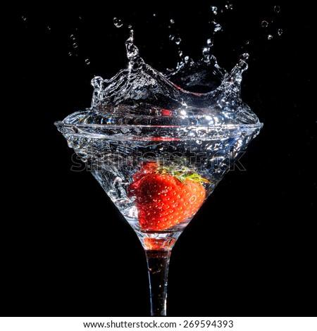 Strawberry splashing into glass of martini on a black background - stock photo