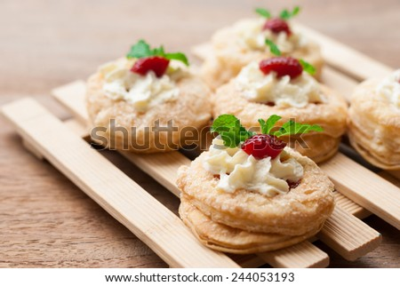 Strawberry Tart with Fresh Cream in Puff Pastry on wooden background - stock photo