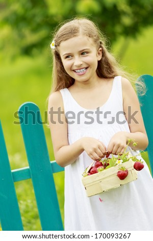 Strawberry time - young girl with picked strawberries in the garden - stock photo