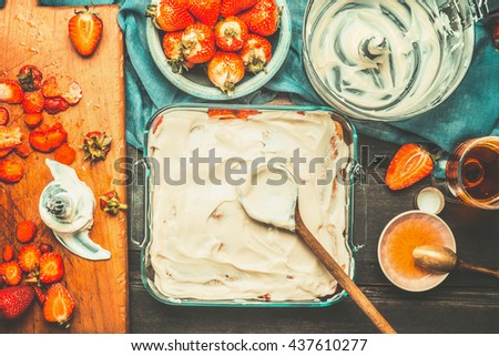 Strawberry tiramisu cake making with cake dish , wooden spoon and mascarpone cream on dark  rustic background, top view. Italian food concept - stock photo