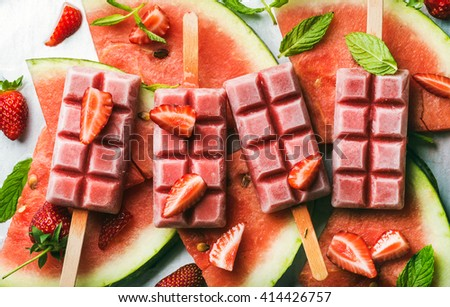 Strawberry watermelon ice cream popsicles with mint over steel tray background. Top view, horizontal - stock photo